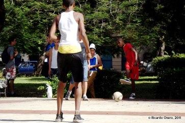 Niños jugando futbol en un parque
