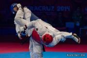 El campeón mundial de taekwondo, Uriel Adriano, recibe una patada en la cara durante su combate de Cuartos de Final de Veracruz 2014. Aunque ganó ese combate, Uriel cayó en la Semifinal y se tuvo que conformar con una medalla de bronce.